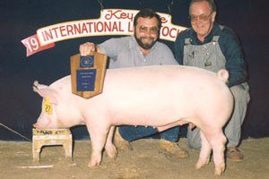 Dave Hosterman (left) and Vernon Hazlett (right), long time swine herdsmen at Penn State, with a show winner.