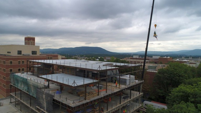 The final beam, with a small tree attached, is hoisted to the top of the half-completed Animal, Veterinary and Biomedical Sciences Building on the University Park campus. The facility is expected to be completed in late 2021. IMAGE: Michael Houtz
