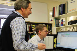 Kevin Harvatine, associate professor of nutritional physiology, seated, and Robert Elkin, professor of avian nutritional biochemistry, review study results.